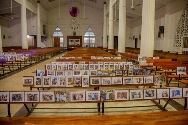 The empty church with the photographs of parishioners attached to the benches.