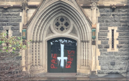 The graffiti on the doors of the Melbourne Cathedral made after the release of Cardinal Pell